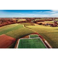 Fußballplatz in Feld-, Wald- und Wiesenlandschaft