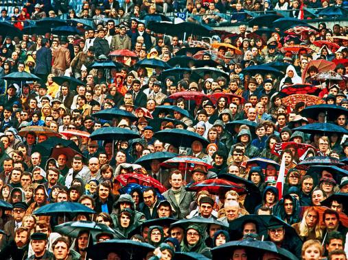 Zuschauer und Regenschirme